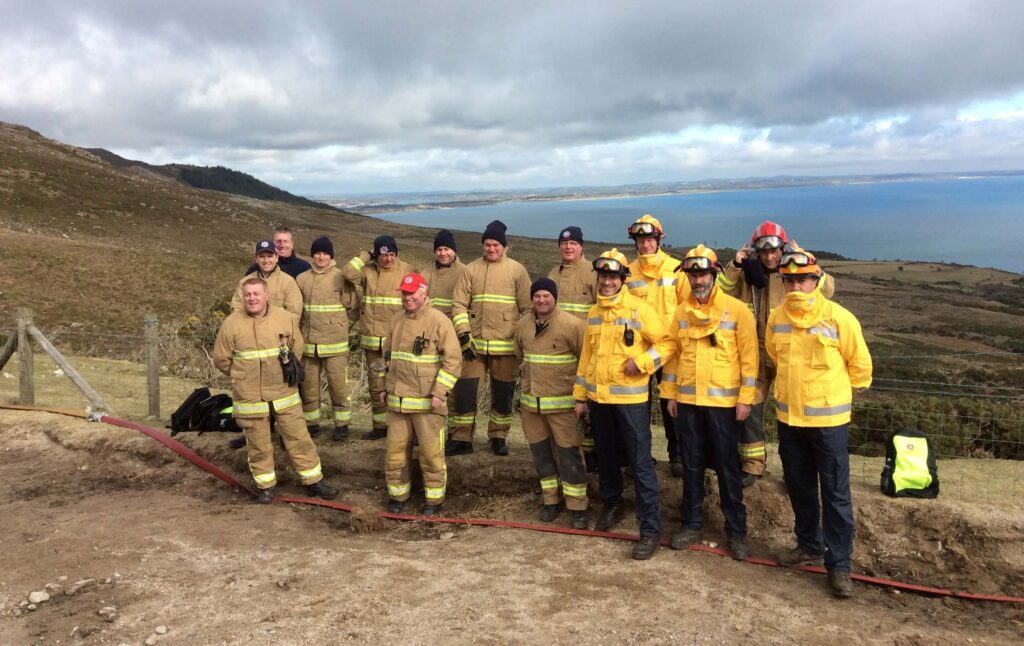 Personnel from NI Fire and Rescue Service and Mourne Heritage Trust (yellow jackets) at a wildfire control plot at Bloody Bridge, Newcastle, Co Down.
